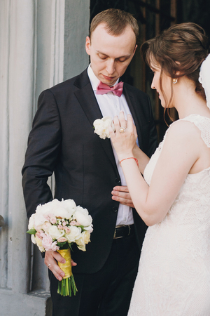 Happy Bride putting on stylish boutonniere on groom suit at doors after wedding ceremony in church. Happy stylish wedding couple during holy matrimony