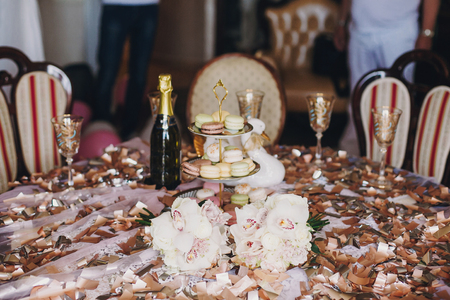 Delicious macarons on beautiful vintage stand and champagne glasses on table with gold  confetti, bouquets, duck. Luxury catering. Bridal hen or baby shower. Festive celebration