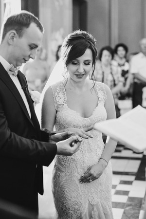 Happy stylish wedding couple exchanging wedding rings during holy matrimony in church. Bride and groom putting on golden rings Stock Photo