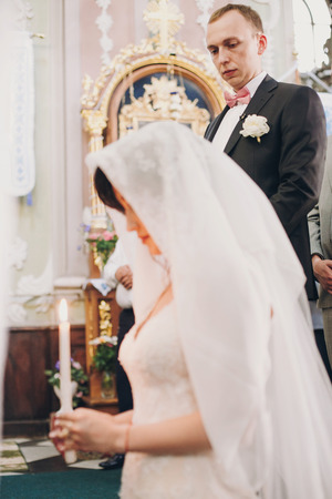 Groom looking at his bride under veil while she is praying with candle light. Happy stylish wedding couple holding candles  during holy matrimony in church.