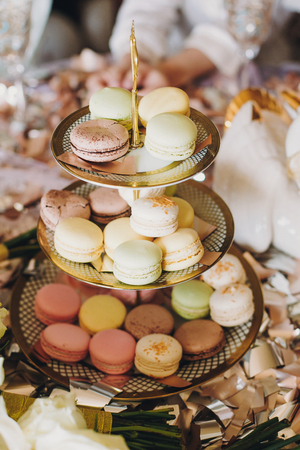 Delicious colorful macarons on beautiful vintage stand with gold ornaments on table with gold and silver confetti. Luxury catering. Bridal hen or baby shower. French dessert macaroons Stockfoto