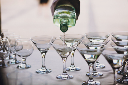 Waiter pouring martini in crystal glasses on table party at wedding reception. Martini row drinks at alcohol bar. Christmas and New Year feast. Celebrations and party concept.