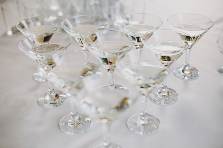 Martini row on table party at wedding reception. Martini drinks in crystal glasses at alcohol bar. Christmas and New Year feast. Celebrations and party concept. Stockfoto