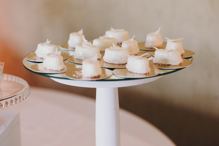 Delicious desserts and sweets on table party at wedding reception. White and pink stylish candy bar. Christmas and New Year feast. Celebrations and party concept