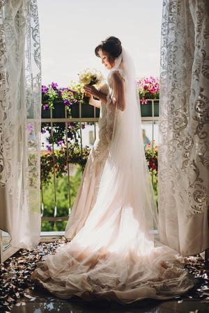 Wunderschöne Braut in tollem Kleid und mit Hochzeitsstrauß, die auf dem Balkon in Blumen und sonnigem Licht posiert. Schöne Frau, die sich morgens fertig macht. Hochzeitsvorbereitungen Standard-Bild