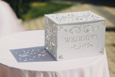 Stylish modern wedding wooden box for gifts,money,presents,wish card for bride and groom from guests  at wedding reception outdoors.