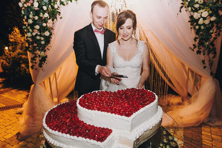 Gorgeous bride and stylish groom cutting together delicious wedding cake in two hearts shape with fresh strawberries at wedding reception in restaurant. Luxury catering