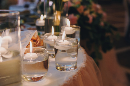 Candles with lights in glasses with water, stylish wedding decor for evening ceremony or at reception in restaurant. Spiritual holy romantic moments Standard-Bild - 114081191