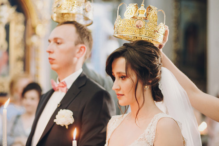 Happy stylish wedding couple holding candles with light under golden crowns during holy matrimony in church. Bride and groom standing at wedding ceremony Stock Photo