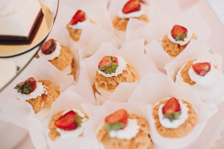Delicious eclairs cupcakes, desserts and sweets on table party at wedding reception. White and pink stylish candy bar. Christmas and New Year feast. Celebrations and party concept.