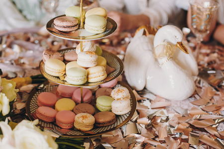 Delicious macarons on beautiful vintage stand and champagne glasses on table with gold and silver confetti and duck. Luxury catering. Bridal hen or baby shower. Festive celebration