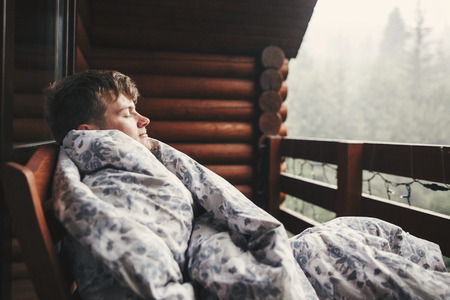 Happy traveler man resting in blanket on wooden porch with view  on woods and mountains. Space for text. Hipster relaxing in wooden cabin in forest. Travel and vacations. Stockfoto