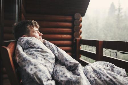 Uomo felice del viaggiatore che riposa in coperta sul portico di legno con vista sui boschi e sulle montagne. Spazio per il testo. Hipster rilassante in cabina di legno nella foresta. Viaggi e vacanze.
