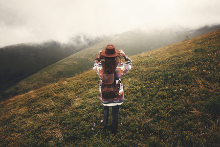 Stylish hipster girl in hat walking on top of mountains. Happy young woman with backpack exploring misty mountains. Travel and wanderlust concept. Amazing atmospheric moment Stock fotó - 114082416