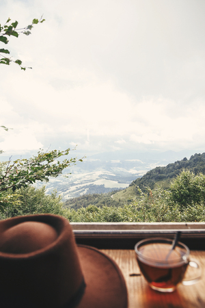 Hot tea in glass cup and hipster hat on background of  beautiful landscape of woods and mountains. View from wooden window on mountain. Space for text. Travel and vacations Imagens