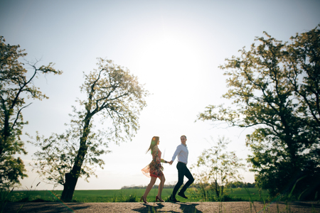 Beautiful young couple holding hands and running in sunshine in spring field and trees. Silhouettes of happy family having fun  in sunlight. Romantic joyful moments. Space for text Stock Photo