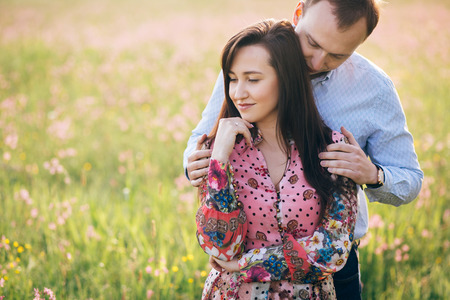 Beautiful young couple gently hugging and kissing in sunshine in fresh spring meadow with pink flowers. Happy stylish family embracing in green field. Romantic moments. Valentine day Stock Photo
