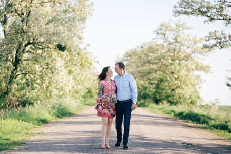 Beautiful young couple holding hands and walking on road in sunshine among spring field and trees. Happy family in love relaxing  in sunlight. Romantic joyful moments. Space for text Standard-Bild