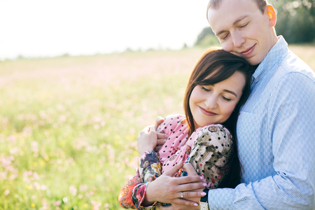 Beautiful young couple gently hugging in sunshine in spring meadow. Happy stylish family embracing in green field with flowers. Romantic moments. Spring. Copy space