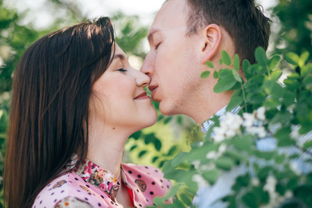 Beautiful young couple gently hugging and kissing at green leaves and white flowers in spring garden. Happy family embracing at blooming acacia tree in sunlight. Romantic moments Stock Photo