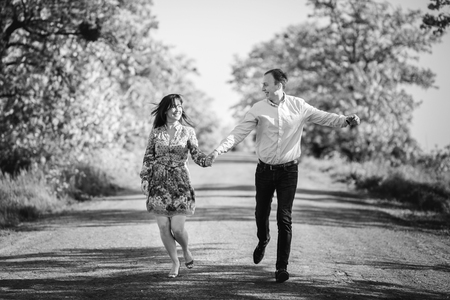 Beautiful young couple running holding hands in spring meadow. Happy stylish family having fun on road at  field trees. Romantic moments. Spring. Black and white photo