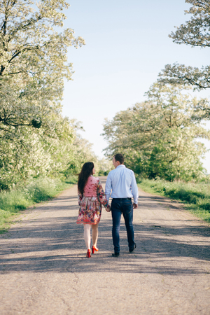 Beautiful young couple holding hands and walking on road in sunshine among spring field and trees. Happy family in love relaxing  in sunlight. Romantic joyful moments. Space for text Stock Photo