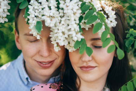 Beautiful young couple posing and smiling under white flowers in spring garden. Portraits of happy family embracing at blooming acacia tree in sunlight. Romantic moments. Valentine day