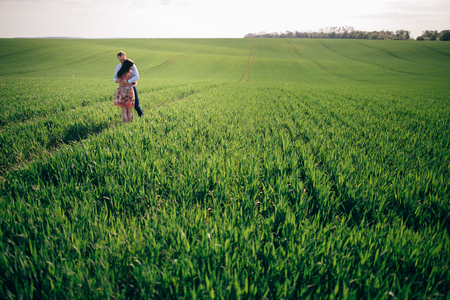 Beautiful young couple gently hugging in sunshine in spring green field. Happy family embracing in green meadow with fresh grass in sunlight. Romantic moments. Space for text