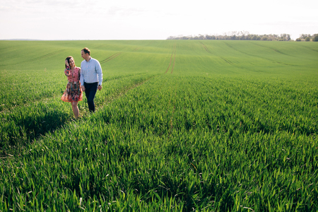 Beautiful young couple holding hands and walking in sunshine in spring meadow. Happy family embracing in green field in sunlight. Romantic moments. Valentine day. Space for text Stok Fotoğraf