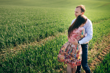 Beautiful young couple gently hugging in sunshine in spring green field. Happy family embracing in green meadow with fresh grass in sunlight. Romantic moments. Valentine day.