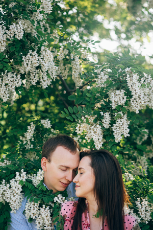Beautiful young couple gently hugging in green leaves and white flowers in spring garden in sunshine. Happy family embracing at blooming acacia in sunlight. Romantic moments.