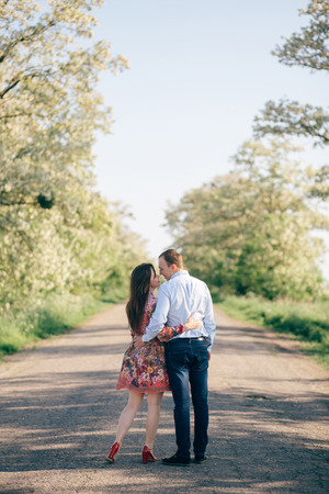 Beautiful young couple holding hands and walking on road in sunshine among spring field and trees. Happy family in love relaxing  in sunlight. Romantic joyful moments. Space for text 免版税图像