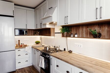 Stylish kitchen interior design. Luxury modern kitchen furniture in grey color and steel oven,fridge, sink, wooden tabletop, pots,. Gray cabinets in scandinavian style. Home renovation. Stock fotó