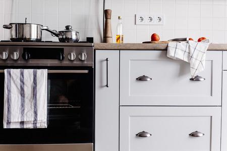 Kochen von Speisen in moderner Küche mit Stahlofen, Töpfen, Messer auf Holzbrett mit Gemüse, Pfeffer, Gewürzen, Öl auf Holztischplatte. Essen zu Hause. Stilvolle Küchenmöbel in grauer Farbe