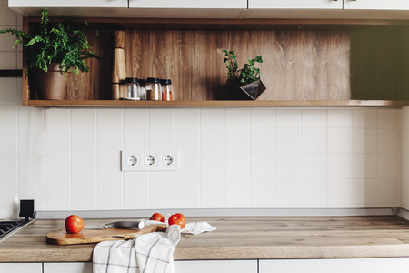Cooking food on modern kitchen with furniture in grey color and wooden tabletop.  Knife on wooden cutting board with vegetables, pepper, spices. Stylish kitchen interior  in scandinavian style Stockfoto - 114851521