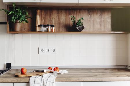 Cucinare il cibo sulla cucina moderna con mobili di colore grigio e piano in legno. Coltello su tagliere di legno con verdure, pepe, spezie. Interni eleganti della cucina in stile scandinavo