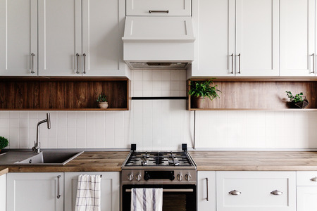 Luxury modern kitchen furniture in grey color and steel oven, sink, wooden tabletop and floor. Gray cabinets in scandinavian style. Home renovation. Stylish kitchen interior design.
