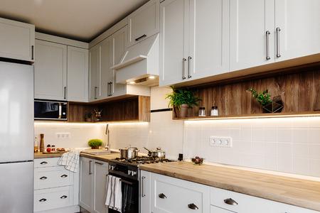 Stilvolle Kücheneinrichtung. Luxuriöse moderne Küchenmöbel in grauer Farbe und Stahlofen, Kühlschrank, Spüle, Holztischplatte, Töpfe, Graue Schränke im skandinavischen Stil. Renovierung des Hauses.