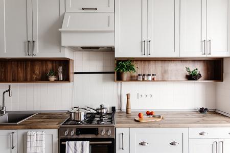 Cuisiner des aliments dans une cuisine moderne avec des meubles de couleur grise et une table en bois. Couteau sur planche à découper en bois avec légumes, poivre, épices. Intérieur de cuisine élégant dans un style scandinave Banque d'images