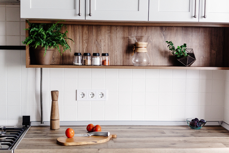 Cooking food on modern kitchen with furniture in grey color and wooden tabletop. Knife on wooden cutting board with vegetables, pepper, spices. Stylish kitchen interior in scandinavian style