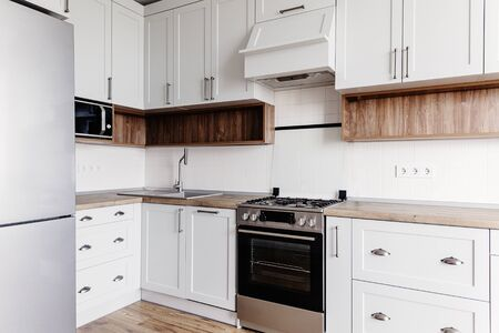 Luxury modern kitchen furniture in grey color and steel oven,fridge, sink, wooden tabletop. Gray cabinets in scandinavian style. Home renovation. Stylish kitchen interior design.