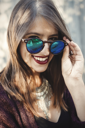 Stylish hipster girl smiling in sunny street on background of wooden wall. Portrait of boho girl in cool outfit and sunglasses posing in sunlight and shadow.  Summer vacation and travel Stockfoto