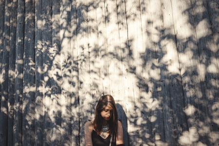 Stylish hipster girl posing in sunny street on background of wooden wall. Boho girl in cool outfit standing in sunlight and shadow. Space for text. Summer vacation and travel. Creative photo