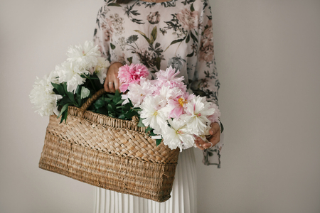 Boho girl holding pink and white peonies in rustic basket. Stylish hipster woman in bohemian floral dress gathering peony flowers. Happy mothers day. International Womens Day. Stock fotó