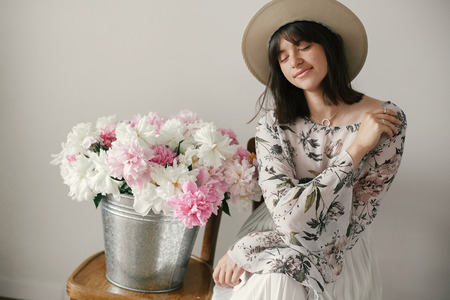 Stylish boho girl in hat sitting at metal bucket with peonies on rustic wooden chair.Beautiful hipster woman posing with big peonies bouquet. Countryside living. International Womens Day