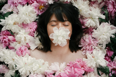 Beautiful brunette girl with white peony in mouth lying in pink peonies. Aroma and care concept. International Womens Day. Creative art floral photo. Portrait of boho woman in many flowers