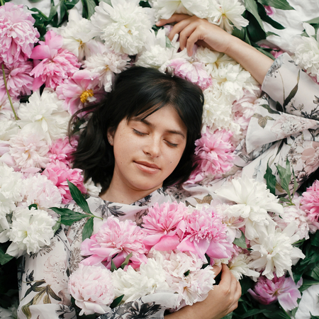 Beautiful brunette girl in many pink and white peonies. Happy boho woman portrait with peony flowers, top view. Creative floral photo. Aroma scent concept. International Womens Day Stock fotó