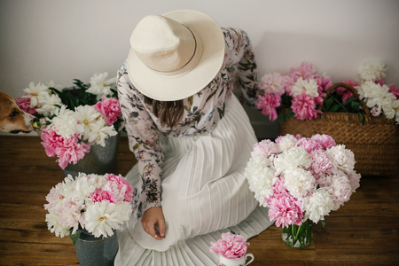 Boho girl sitting with her dog at pink and white peonies on rustic wooden floor. Stylish hipster woman in hat and bohemian floral dress  with flowers. Countryside living Stock fotó
