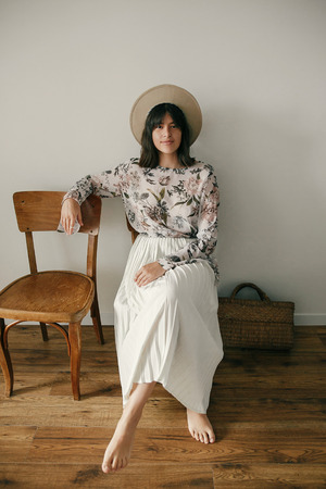 Beautiful brunette boho girl in hat sitting on rustic wooden chair in home. Stylish hipster woman posing in bohemian dress. International Womens Day. Countryside living