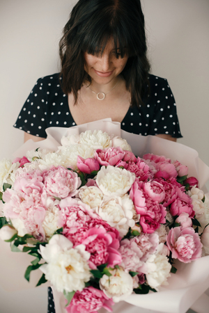 Beautiful brunette girl in vintage dress holding big bouquet with pink and white peonies. Happy stylish woman with peony flowers in room. International Womens Day